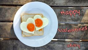 Fried eggs in the shape of a heart at toast on white plate and wooden table. Breakfast with love. Inscription Happy Valentine`s. Day royalty free stock images