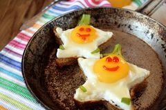 Fried eggs shaped as stars with funny faces. In a pan Royalty Free Stock Photo