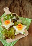 Fried eggs shaped as stars with funny faces. On salad leaves. Breakfast for kids Stock Photos