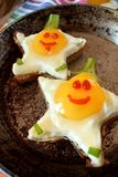 Fried eggs shaped as stars with funny faces. In a pan Royalty Free Stock Photography