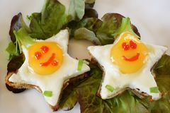 Fried eggs shaped as stars with funny faces. On salad leaves. Breakfast for kids Royalty Free Stock Image