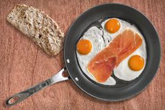 Fried Eggs and Smoked Ham Rasher in Frying Pan with Slice of Bread on Cherry Wood Background Royalty Free Stock Photography