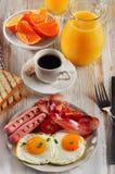Fried Eggs, Speck, Würste und frischer Orangensaft Stockfotografie