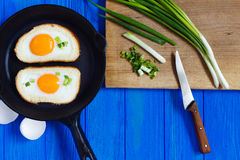 Fried eggs and spring onion on wooden chopping board Stock Photography