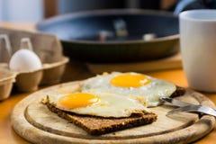 Fried Eggs su pane nero e su caffè - prima colazione Immagini Stock Libere da Diritti
