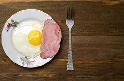 Fried eggs sunny side up on a plate on a wooden background Stock Image