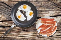 Fried Eggs in Teflon Frying Pan with Plateful of Prosciutto Ham Slices on Old Picnic Wooden Table Royalty Free Stock Image