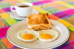 Fried eggs and toasts and coffee cup background Stock Photos