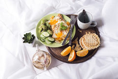 Fried eggs with toasts and tea in bed Royalty Free Stock Image
