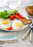 Fried Eggs with tomato, lettuce and bread on a white plate Royalty Free Stock Photos