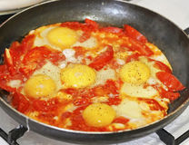 Fried eggs with tomato on the pan Royalty Free Stock Photo