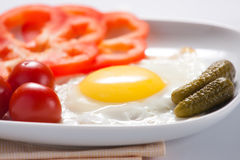 Fried eggs with tomatoes and cucumbers. Fried eggs with tomatoes, cucumbers and pepper Royalty Free Stock Photos