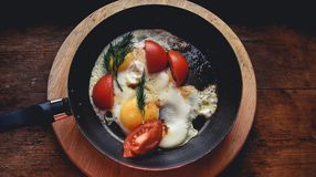 Fried eggs with tomatoes and dill fried in a pan in a rustic style. antique wood window sill stand royalty free stock photos