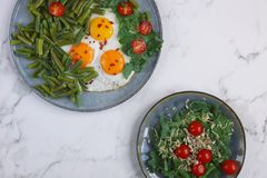 Fried eggs in with tomatoes, green beans, pepper and salad on a marble background, Healthy food, Fitness salad royalty free stock photo
