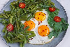 Fried eggs in with tomatoes, green beans, pepper and salad on a marble background, Healthy food, Fitness salad royalty free stock image