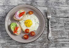 Fried eggs, tomatoes and sandwiches with cucumber, radish and soft cheese. On a light wooden table. Rustic style. Stock Photos