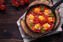 Fried eggs with tomatoes and vegetables. Shakshuka in a cast iron portioned pan on a wooden background top view