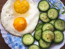 Fried eggs from two eggs with cucumbers on a ceramic plate Royalty Free Stock Photos