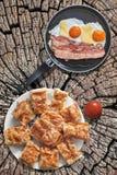 Fried Eggs- und Speck-Speckschnitten in der Teflonbratpfanne mit Tomate und Tellervoll Gibanica-Käse-Torten-Scheiben eingestellt  Lizenzfreie Stockfotografie