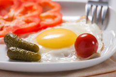 Fried eggs with vegetables. Fried eggs with tomatoes, cucumbers and pepper Stock Image