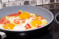 Fried eggs with vegetables in a frying pan Stock Photo