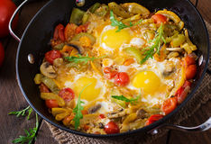 Fried eggs with vegetables in a frying pan. Royalty Free Stock Photo