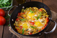 Fried eggs with vegetables in a frying pan. Stock Photo