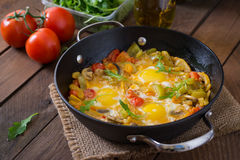 Fried eggs with vegetables in a frying pan. Stock Image