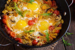 Fried eggs with vegetables in a frying pan. Stock Images