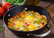 Fried eggs with vegetables in a frying pan. Royalty Free Stock Photos