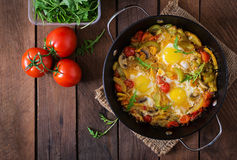 Fried eggs with vegetables in a frying pan on a wooden background. Royalty Free Stock Photography