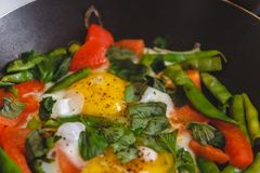 Fried eggs with vegetables and herbs in a pan, on the fire, on the stove, cook. Top view, close-up. Concept, healthy breakfast. Fly lay stock photo