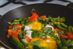 Fried eggs with vegetables and herbs in a pan, on the fire, on the stove, cook. Top view, close-up. Concept, healthy breakfast. Fly lay stock images