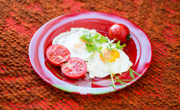 Fried eggs with vegetables on a red plate Royalty Free Stock Image