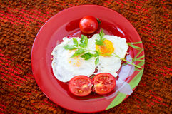 Fried eggs with vegetables on a red plate Royalty Free Stock Photography