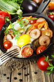 Fried eggs with vegetables and sausage Royalty Free Stock Images