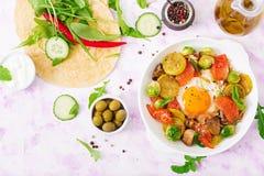 Fried eggs with vegetables - shakshuka and fresh cucumber, watermelon radish and arugula Royalty Free Stock Image