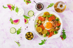 Fried eggs with vegetables - shakshuka and fresh salad cucumber, watermelon radish and arugula. Flat lay. Top view Stock Image