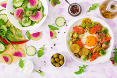 Fried eggs with vegetables - shakshuka and fresh salad cucumber, watermelon radish and arugula. Flat lay. Top view Stock Photos