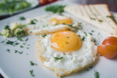 Fried eggs on white plate with green and tomato cherry - breakfast, macro view