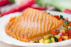 Fried fillet of red fish salmon with roasted vegetables Stock Photo