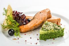 Fried fillet of salmon with spinach. On a white plate stock photos