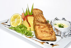 Fried fish. With polenta and lemon on the white plate Stock Image