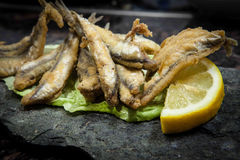 Fried fish. Deep fried anchovies on lettuce leaf and black tray stock photography