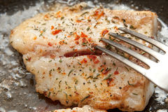 Fried fish. With spices in the cooking pan royalty free stock image