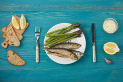 Fried fish and asparagus shoots on a plate top view. Stock Photography