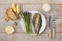 Fried fish with asparagus shoots on a plate, top view. Royalty Free Stock Image