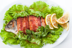 Fried fish and bacon with lettuce and lemon.  on a white backgro Royalty Free Stock Photo