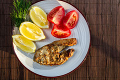 Fried fish in batter served with tomatoes Stock Photos