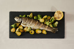 Fried fish. With Brussels sprouts, broccoli and lemon Royalty Free Stock Image